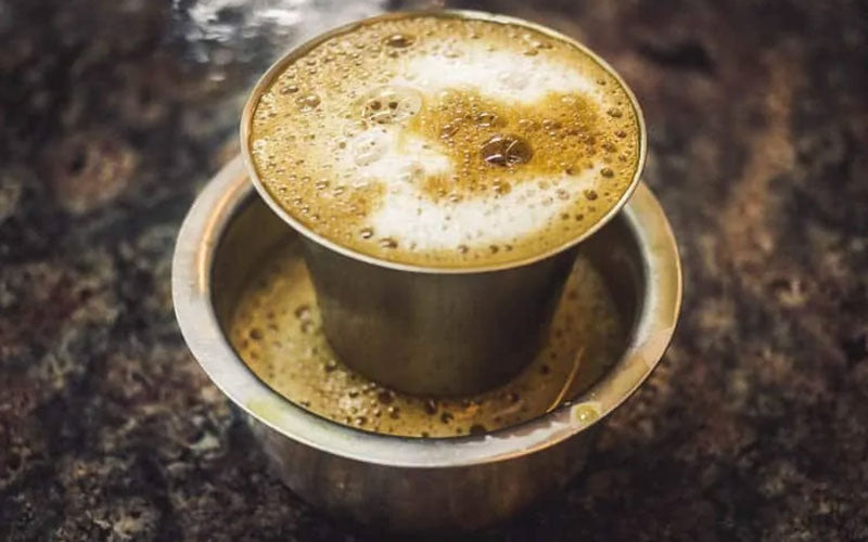 A Kaapi coffee drink, popular in India, sits on a table