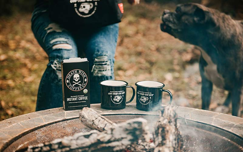 Instant coffee sitting near a campfire with two black mugs.