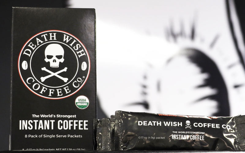 A black box of Death Wish Instant Coffee sits on a table next to individual black packets of Death Wish Instant Coffee