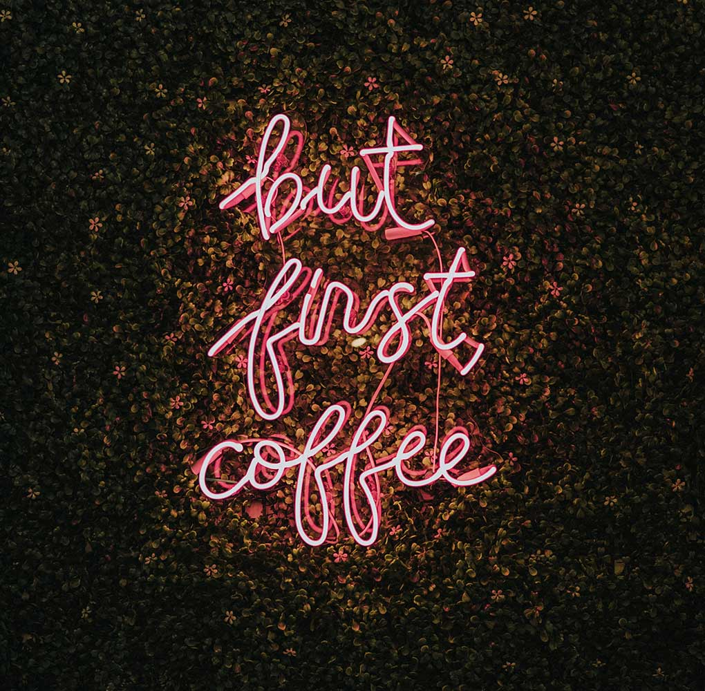 """A neon pink sign that reads """"but first coffee"""" in cursive writing on a garden wall backdrop."""