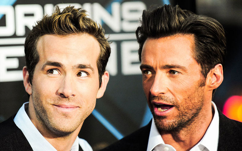 Actors Ryan Reynolds and Hugh Jackman stand next to each other on the red carpet