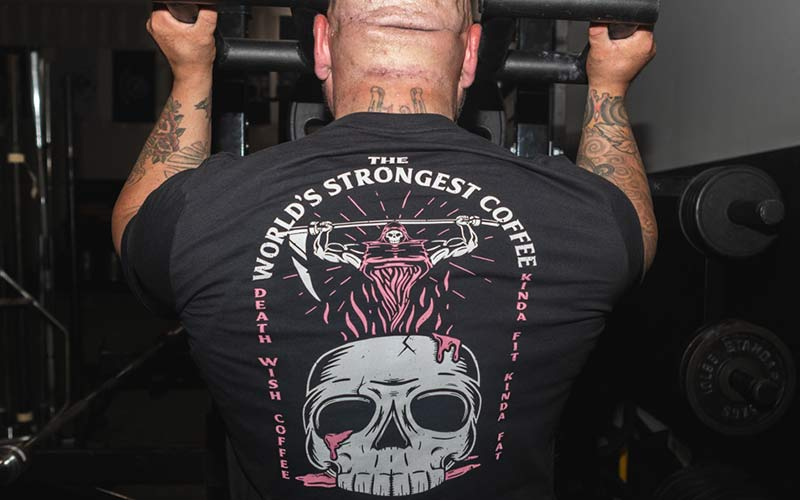 A man lifting weights wearing a tee with a skull and man reaper lifting a sythe.