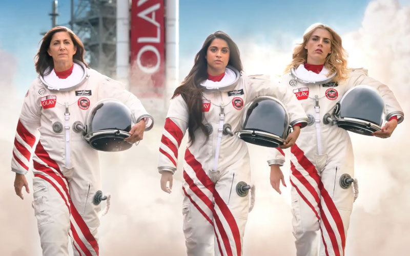 From left to right, Nicole Stott, Lilly Singh, and Busy Philipps dressed in astronaut suits in Olay's Super Bowl spot