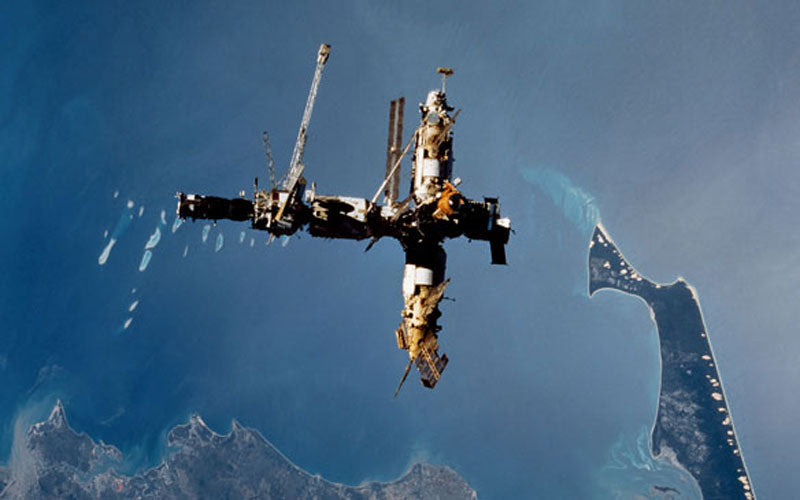 A colored photo of the Mir Space Station floating hundreds of miles above Earth. A small island on Earth is shown in the background.