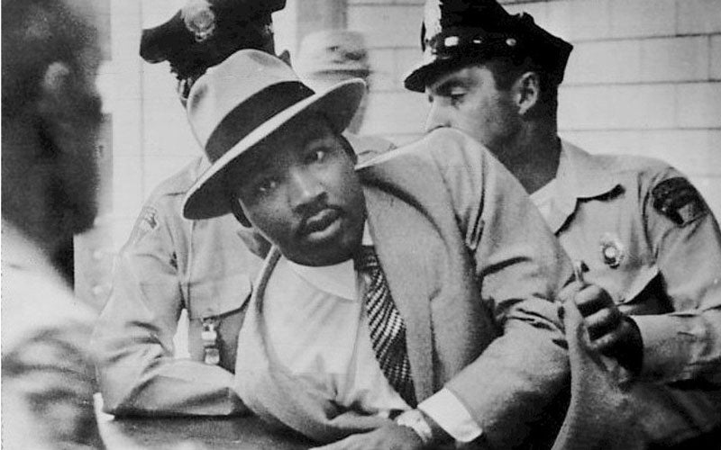 A photo of Dr. Martin Luther King Jr. being apprehended by police