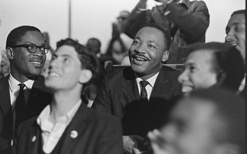 A photo of Dr. Martin Luther King Jr. smiling and sitting in a crowd