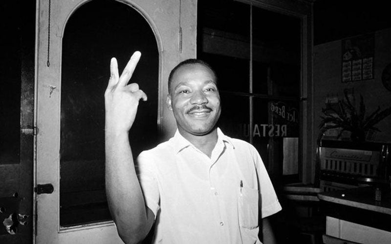 A photo of Martin Luther King Jr. flashing a peace symbol