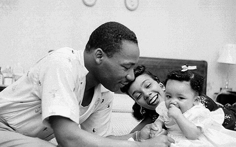 A black and white photo of Martin Luther King Jr. with his wife and his daughter