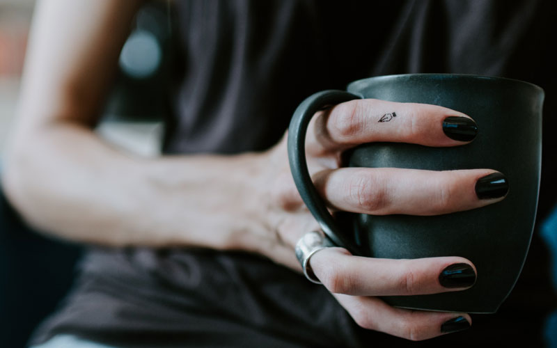 A woman with black nail polish holding a green coffee mug