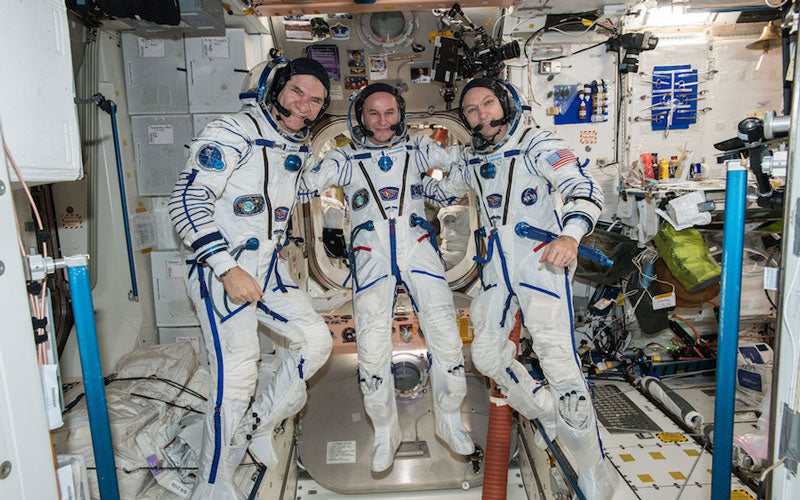 Three astronauts stand next to each other in the International Space Station in full spacesuits