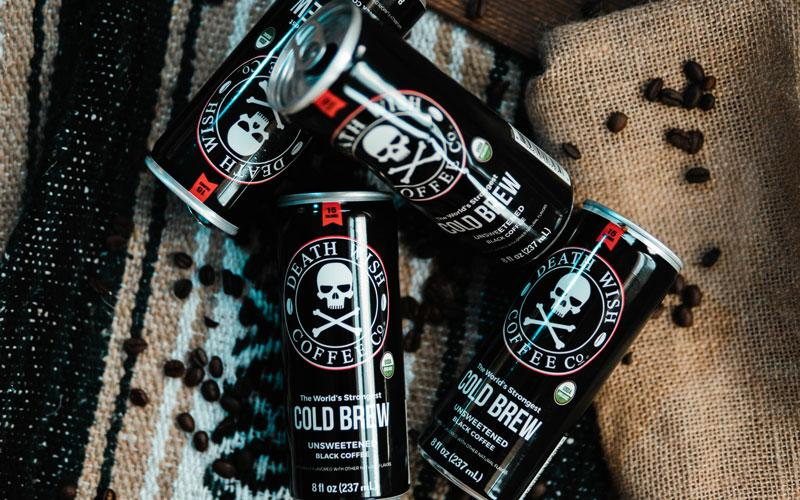 Four black cold brew cans sit on a burlap sack covered in coffee beans
