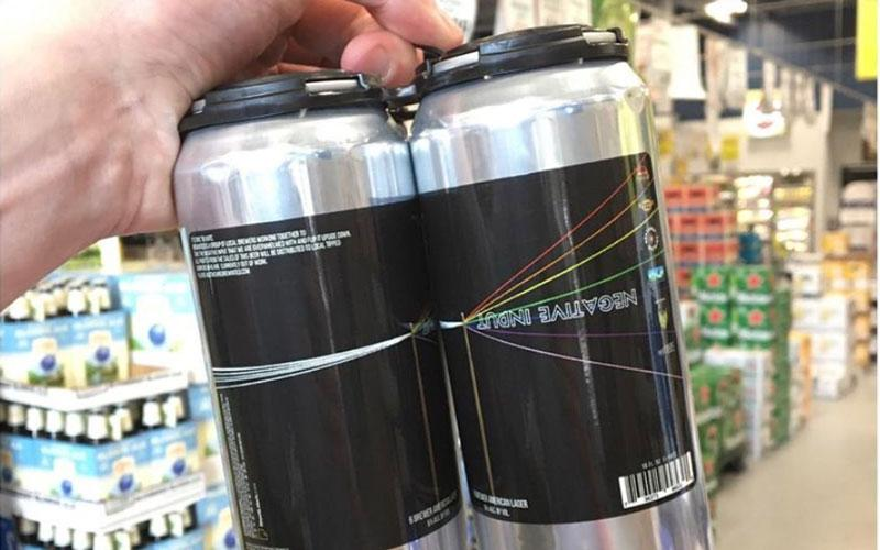 "A first-person view of someone holding a four-pack of ""Negative Input"" beer in black and silver cans"