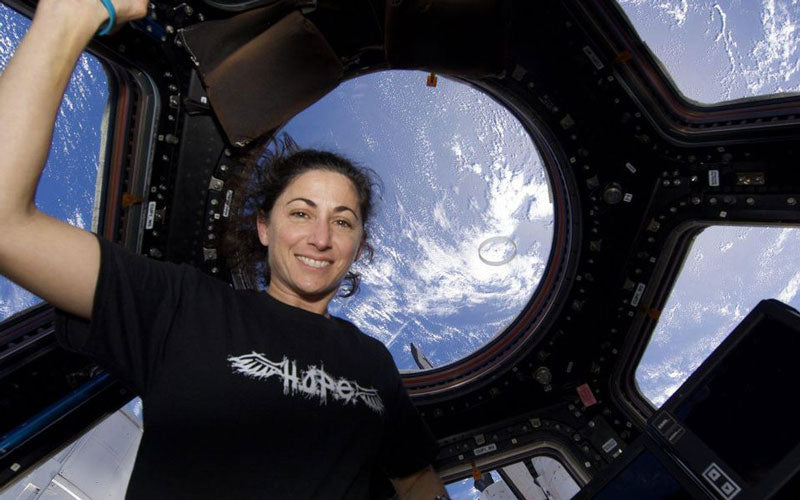 Astronaut Nicole Stott poses for a photo inside the International Space Station, with Earth slightly visible in the background