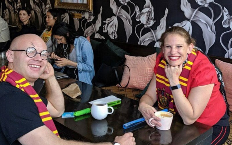 Two customers in red and gold Harry Potter scarves drinking coffee at Nimbus Coffee in Los Angeles