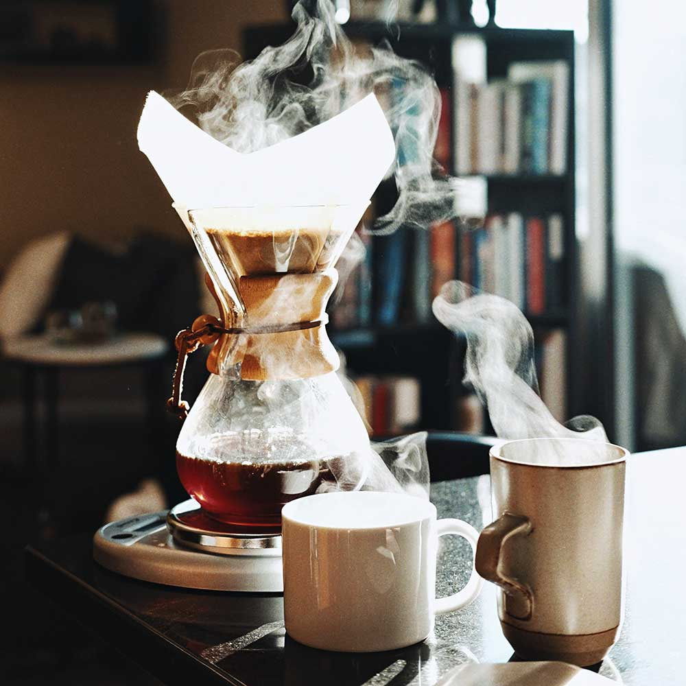 A coffee Chemex and two mugs steaming with hot coffee on a kitchen counter.