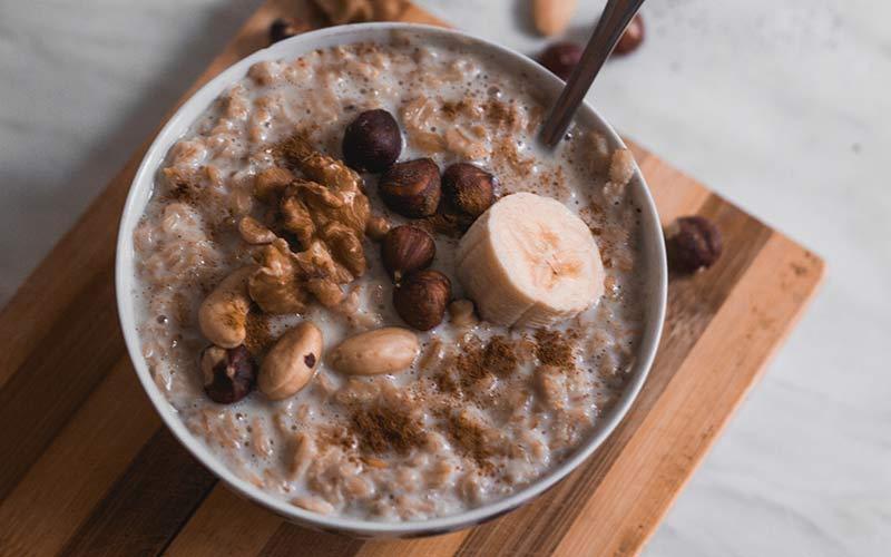 A bowl of oatmeal topped with bananas, nuts and instant coffee.
