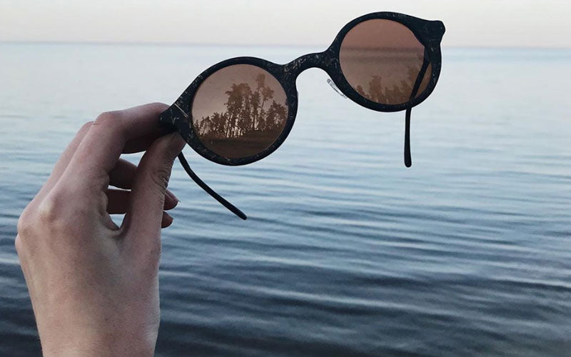 A photo of someone holding a pair of brown glasses made from coffee grounds with a river in the background