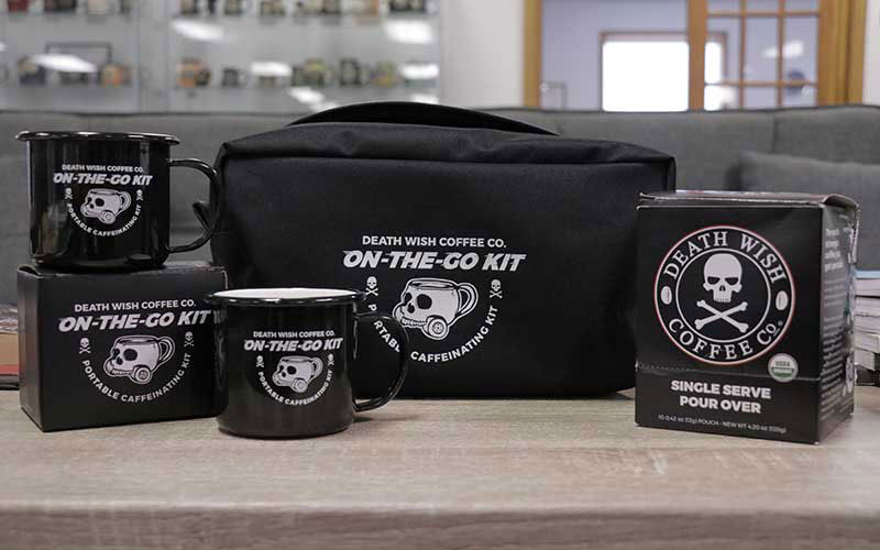A Death Wish On the Go kit sits on a table. This kit shows two mugs, a pack of coffee, and a canvas bag with a Death Wish logo