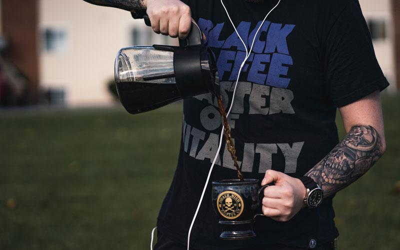 A man with tattoos pouring coffee into a Death Wish Coffee mug