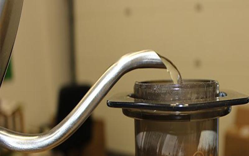 Gooseneck kettle pouring water into container