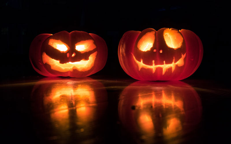 Two lit pumpkin jack o'lanterns carved with scary faces sit on a dark table