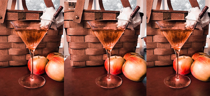 An image of three pumpking spiced martinis with a fall backdrop featuring a basket and apples.