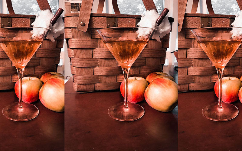 An image of three pumpking spiced martinis in a frosted martini glass with a cinnamon stick as a garnish. The backdrop is fall themed with a picnic basket and a few apples on a table.