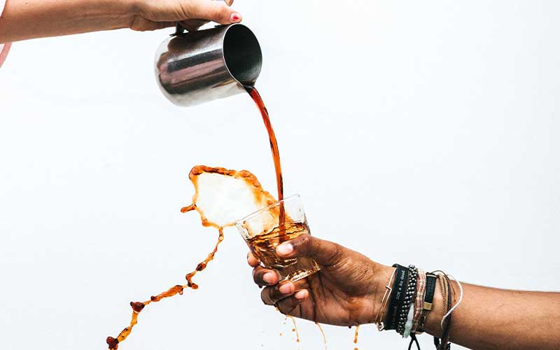 Coffee being poured and spilled over a held out cup