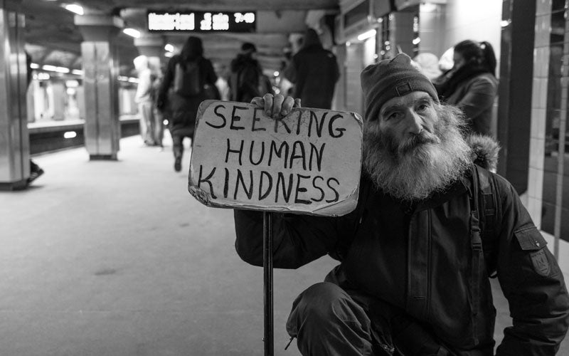 "A black and white photo of a man holding a sign that says ""Seeking Human Kindness"""