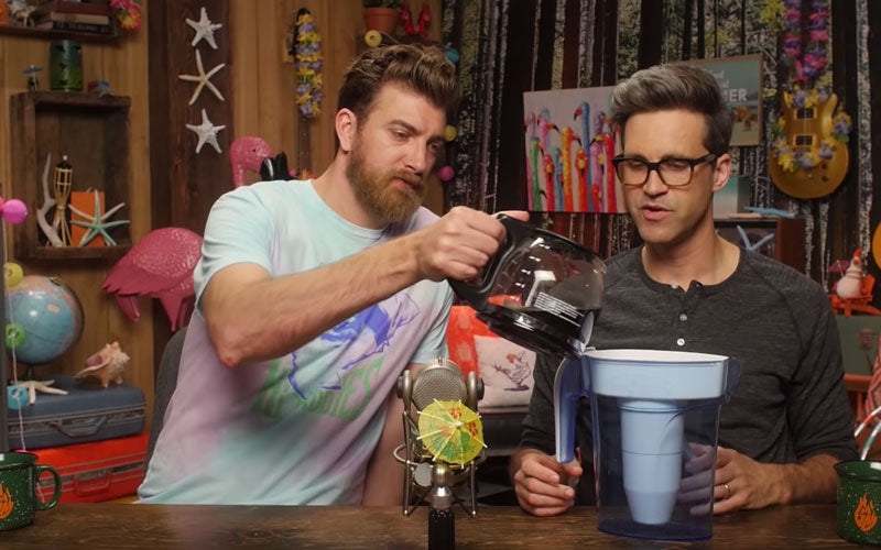 Rhett and Link, the two male hosts of Good Mythical Morning, are pictured pouring coffee through a water filter