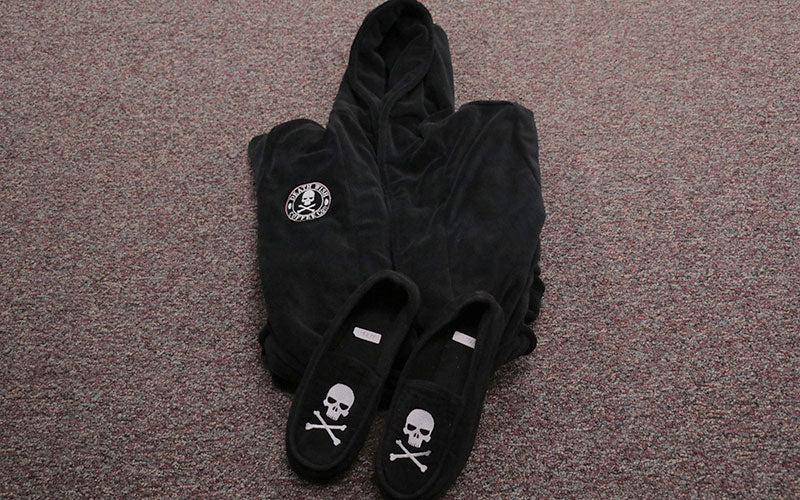 A product photo of a black robe and matching slippers with the Death Wish Coffee skulls and crossbones logo