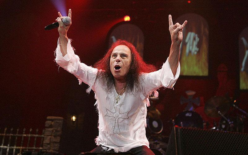 Ronnie James Dio, an iconic musician, stands on stage showing the horns symbol with his hands