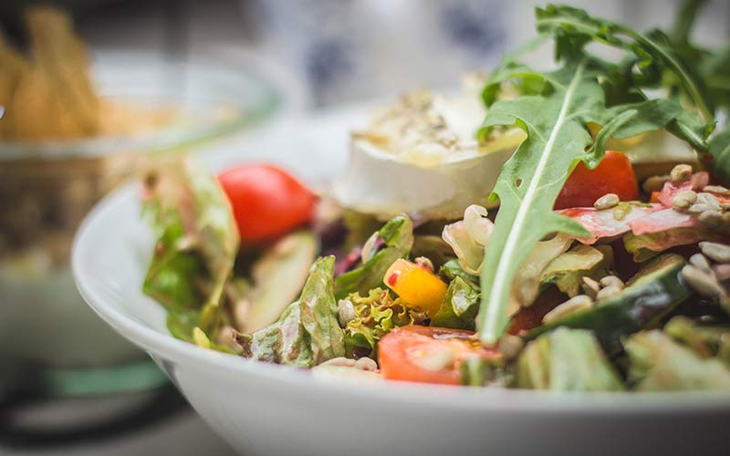 A bowl of salad topped with an instant coffee vinaigrette dressing.