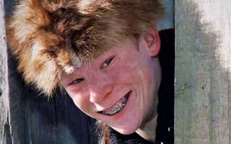 "A screenshot of Scot Farkus, a bully in the movie ""A Christmas Story,"" showing him smile and peer around a corner of a fence in a fur hat"