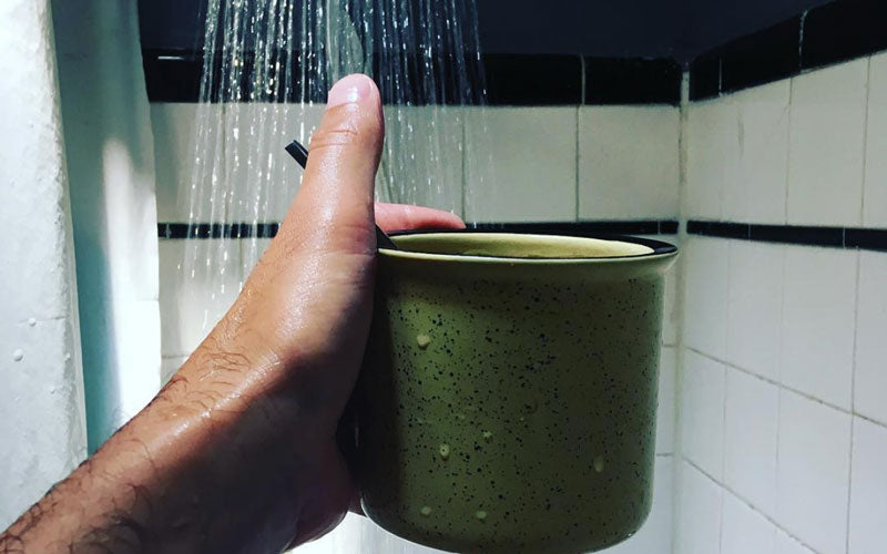 A male hand pictured holding a coffee mug inside of a running shower