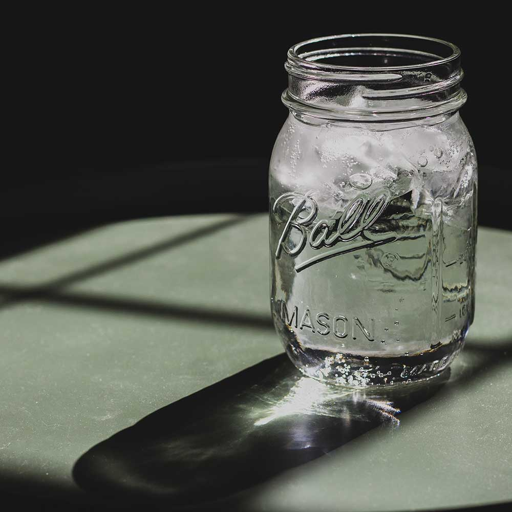 A mason jar filled with water and ice on a green table top.