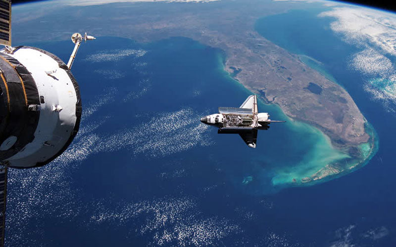 A photo of a space shuttle taken by the International Space Station, where you can see the shuttle floating over the state of Florida