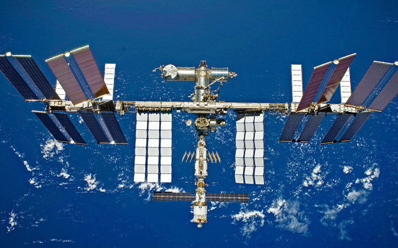 An aerial photo of the International Space Station floating in space above Earth