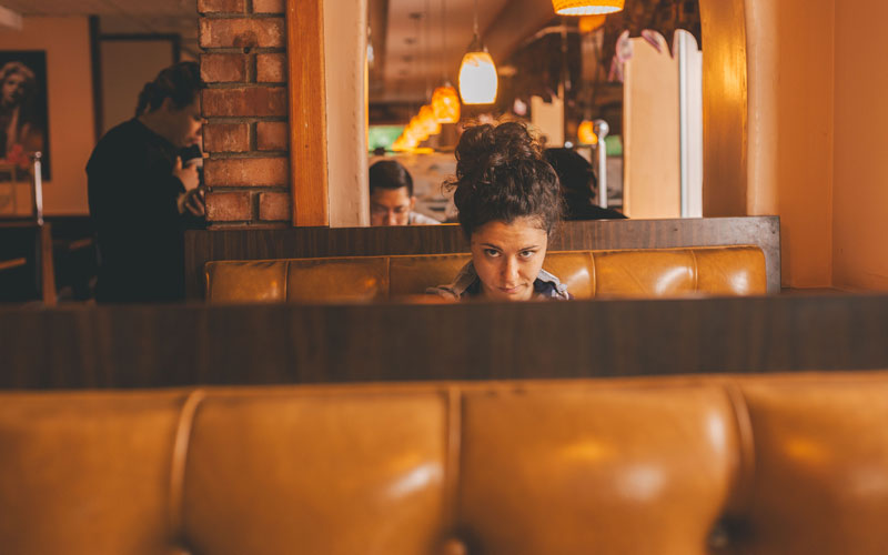 A photo of a woman peering over the top of a brown booth in a diner
