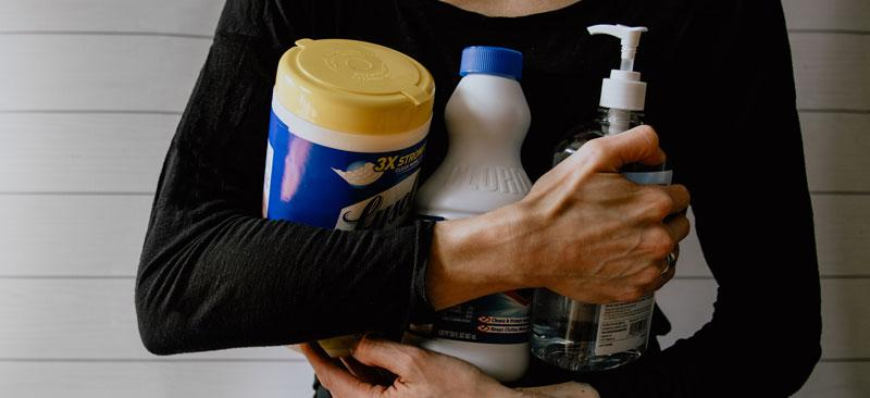 A woman holding cleaning products that include wipes, sanitizer, and bleach