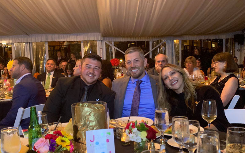 Two Death Wish Coffee employees sit with Barbaranne Wylde at a St. Jude gala in Saratoga Springs, New York