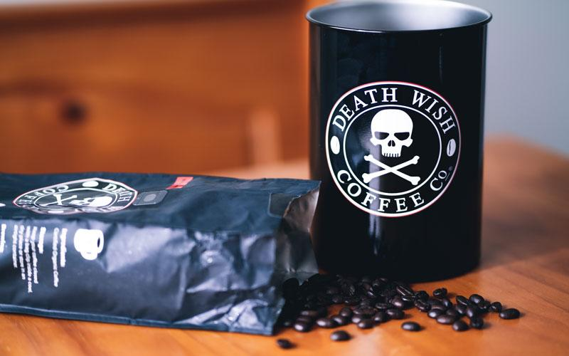 A Death Wish Coffee bag of whole bean coffee next to an air-tight container for storage
