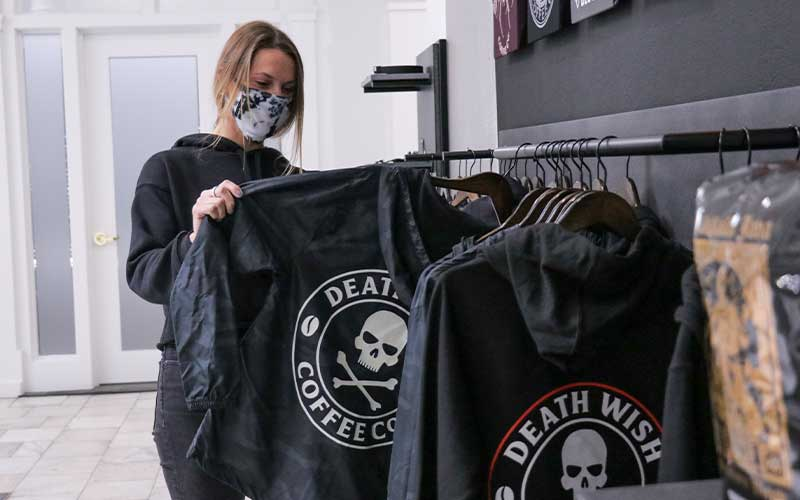Woman examining a jacket at the Death Wish Coffee store