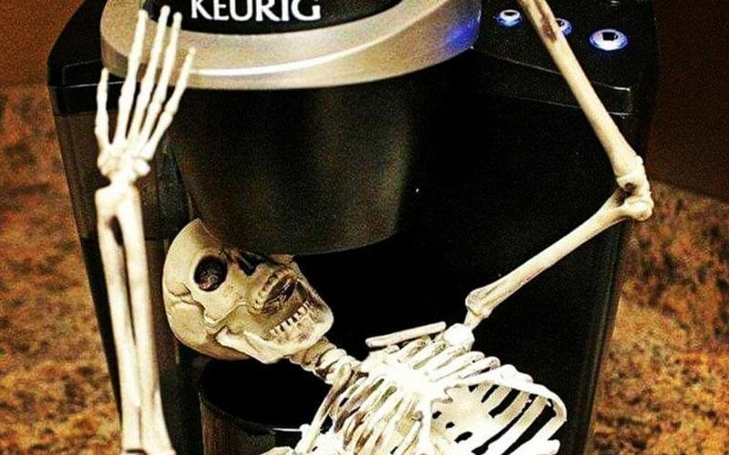 A skeleton shown drinking coffee straight from a Keurig coffee machine