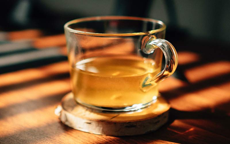 A clear glass containing tea sitting on a coffee table.
