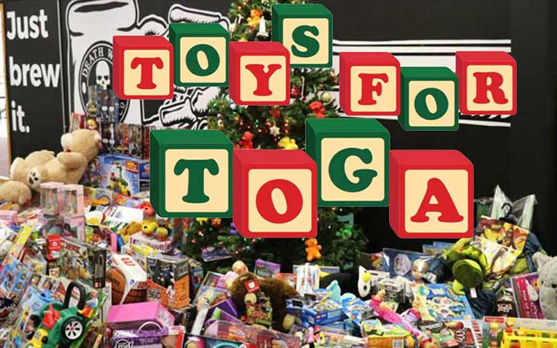Toys under a Christmas tree with Toys for Toga logo overlay
