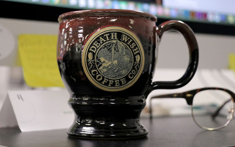 A black and red mug with a Thor and Valkyrie medallion sits on a desk