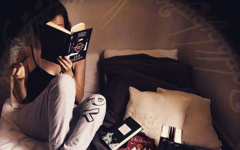 A girl in sweatpants reading a book by JRR Tolkien on her bed