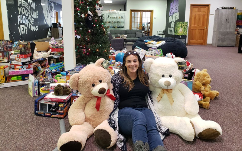 A woman smiles and poses with hundreds of toys in front of a Christmas tree in the Death Wish Coffee Office
