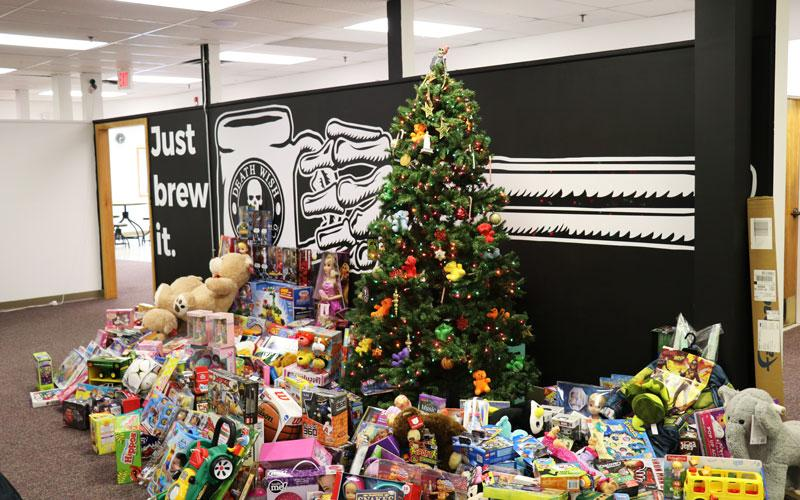 A lit-up Christmas tree in the Death Wish Coffee office with hundreds of toys underneath